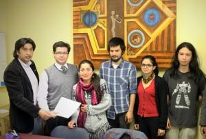 Los alumnos Rosa Umaña, Gabriel Ramos, Camila Araneda y Jorge Lizama hacen entrega del Manual de Convivencia Estudiantil al director de la DDE, Fernando Morales y al jefe del Departamento de Arte, Cultura y Comunicación, Nelson Muñoz.
